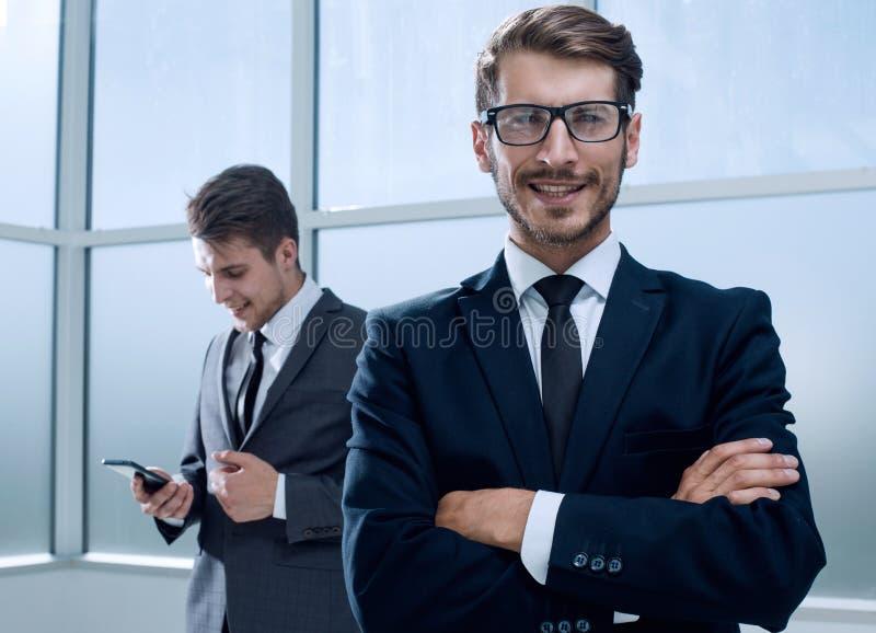 Предприниматели используя технологию в занятой зоне лобби офиса стоковые изображения