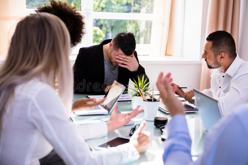 Предприниматели обвиняя их коллеги в офисе стоковые фотографии rf