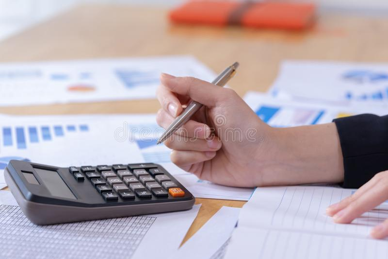 Предприниматель женщины используя калькулятор к высчитывать финансовый расход на офисе стоковое изображение rf