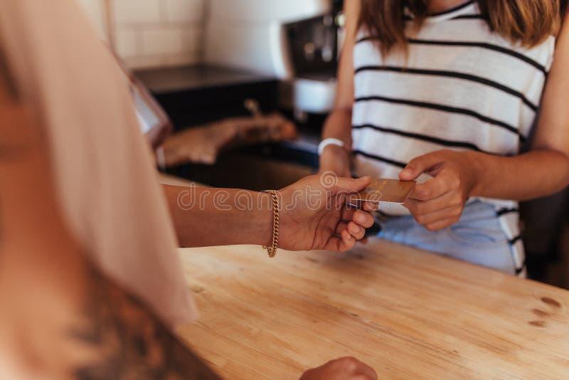 Предприниматель женщины признавая оплату карточкой на coun выписывания счетов стоковая фотография rf