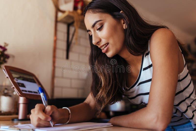 Предприниматель женщины сидя на счетчике выписывания счетов ее кафа стоковая фотография rf