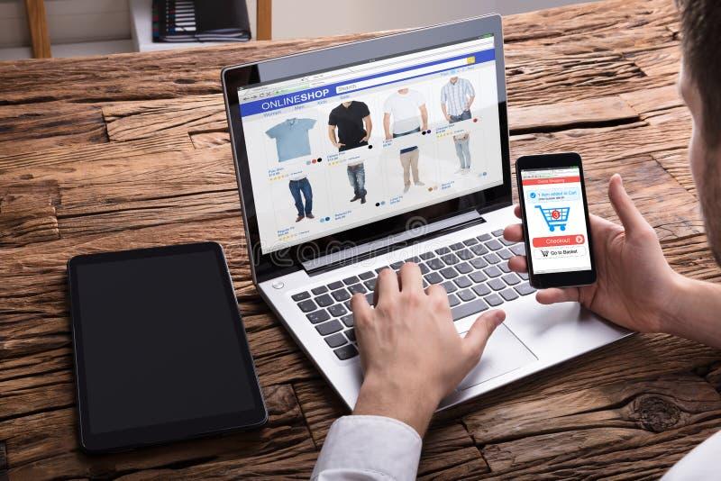 Предприниматель используя Smartphone пока ходить по магазинам онлайн на компьтер-книжке стоковое фото rf