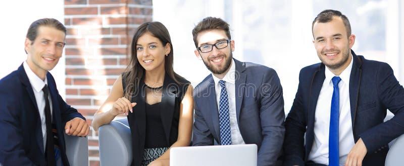 Предприниматель и дело объединяются в команду, сидящ на софе в лобби офиса стоковые изображения rf