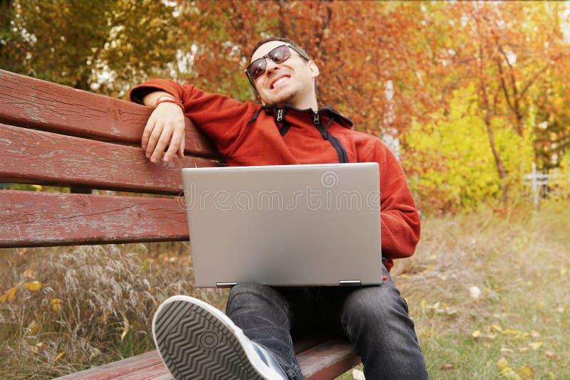 Предприниматель молодого человека празднуя хорошие новости чтения успеха в бизнесе на ноутбуке в парке Удерживание смеха фрилансе стоковое изображение