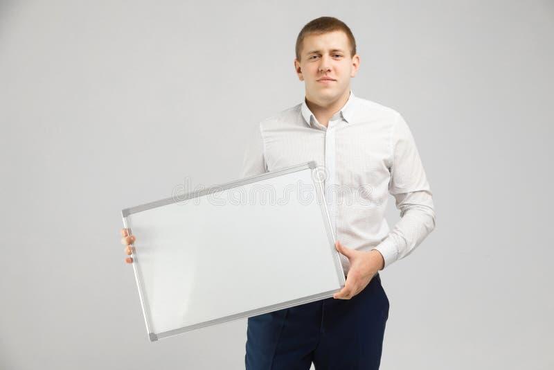 Предприниматель с магнитной доской в его руках на белой предпосылке стоковые изображения rf