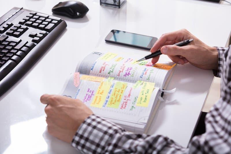 Предприниматель с план-графиком сочинительства мобильного телефона стоковая фотография rf