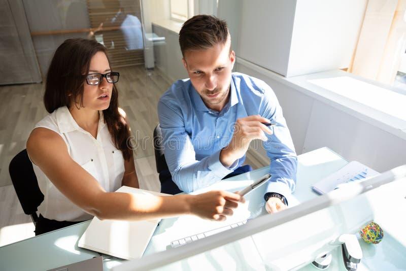 2 предпринимателя смотря компьютер имея разговор стоковое изображение rf