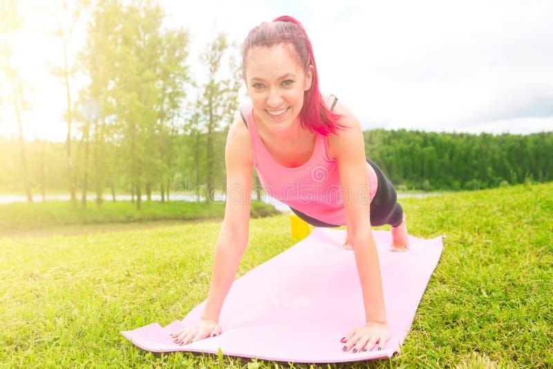Представление девушки йоги практикуя outdoors красивая девушка делая разминку на траве в утре стоковая фотография rf