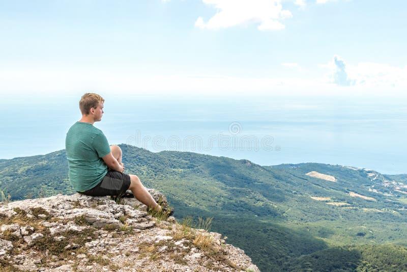 Представление йоги молодого человека практикуя сидя на скалистом пике Человек делает раздумье и наслаждаться взгляд стоковое изображение rf