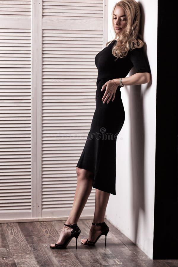 Представлять красивой женщины модельный в элегантном черном платье стоковая фотография rf