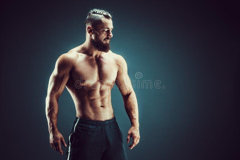 представлять культуриста Человек muscled фитнесом на темной предпосылке стоковое фото rf