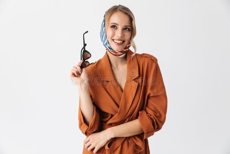 Представлять шарфа шелка счастливой молодой женщины нося стильный изолированный над белой предпосылкой стены держа солнечные очки стоковые изображения rf