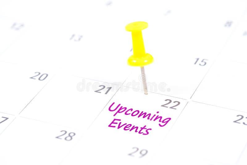 Предстоящие события написанные на календаре с желтым штырем нажима к стоковое изображение rf