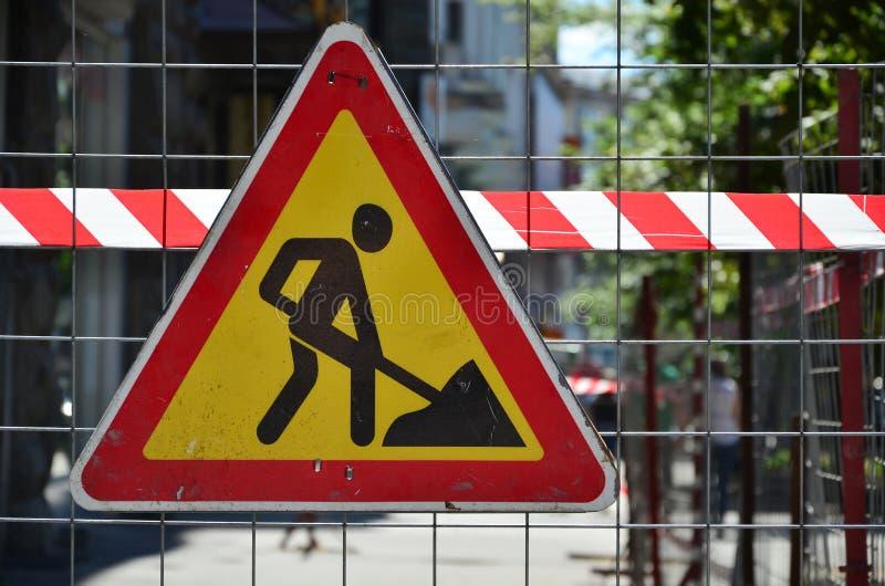 ` Предупредительного знака под ` конструкции прикреплено к загородке сетки металла с красным и белым striped краном сигнала стоковые изображения rf