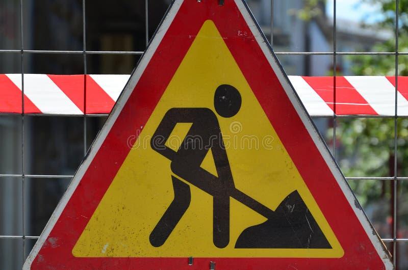` Предупредительного знака под ` конструкции прикреплено к загородке сетки металла с красным и белым striped краном сигнала стоковое фото