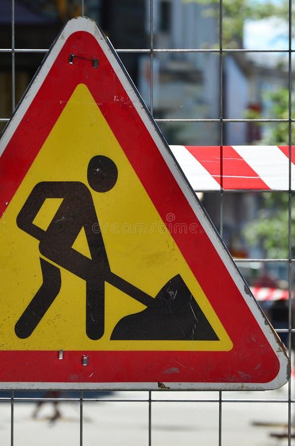 ` Предупредительного знака под ` конструкции прикреплено к загородке сетки металла с красным и белым striped краном сигнала стоковое фото rf