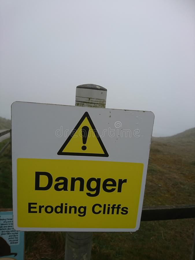 Предупредительные знаки Быть осторожным идя, clifs dander, выветриваясь скалы Праздник Корнуолла Perranporth стоковая фотография rf