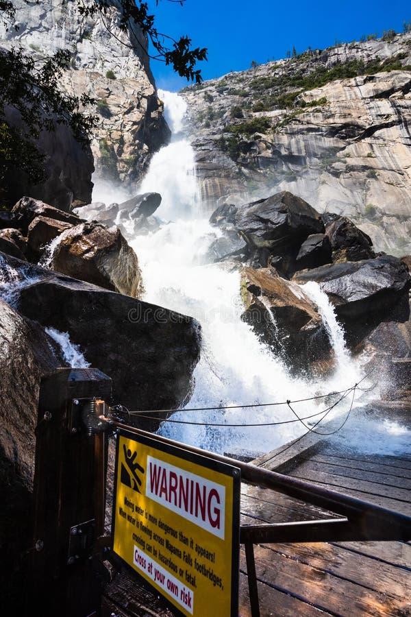 Предупредительный знак должный к падениям Wapama пропуская над footbridge и создавая опасные условия для пересекать; Hetch Hetchy стоковое изображение rf