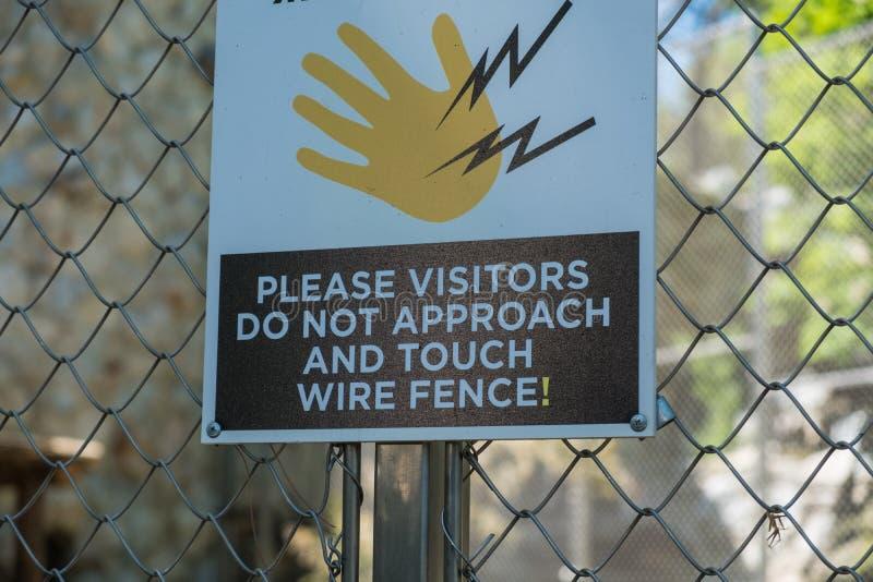 Предупредительный знак на electrified проволочной изгороди в зоопарке стоковое изображение rf