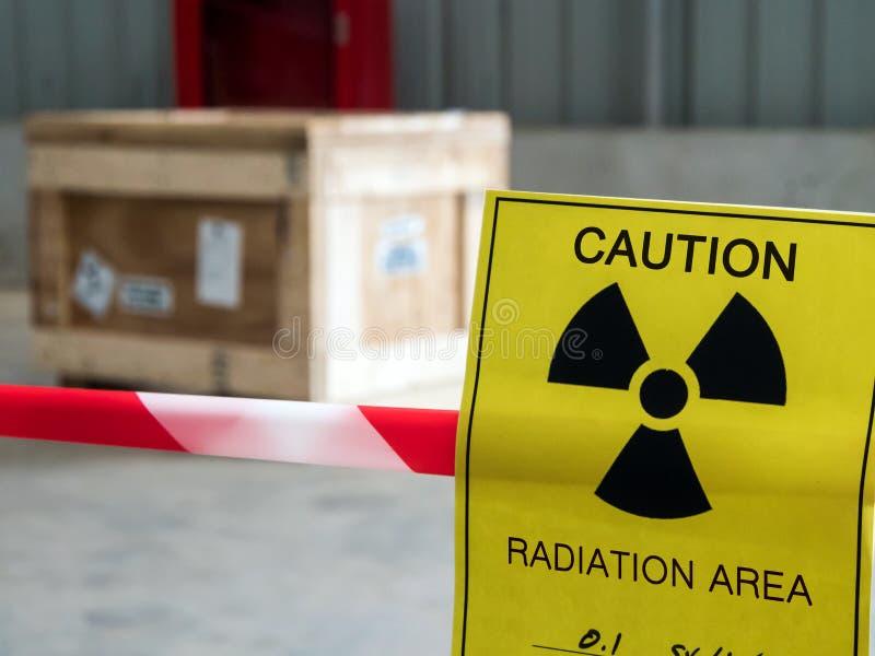 Предупредительный знак радиации на ленте предупреждения зоны вокруг опасного материального пакета в складе фабрики стоковая фотография