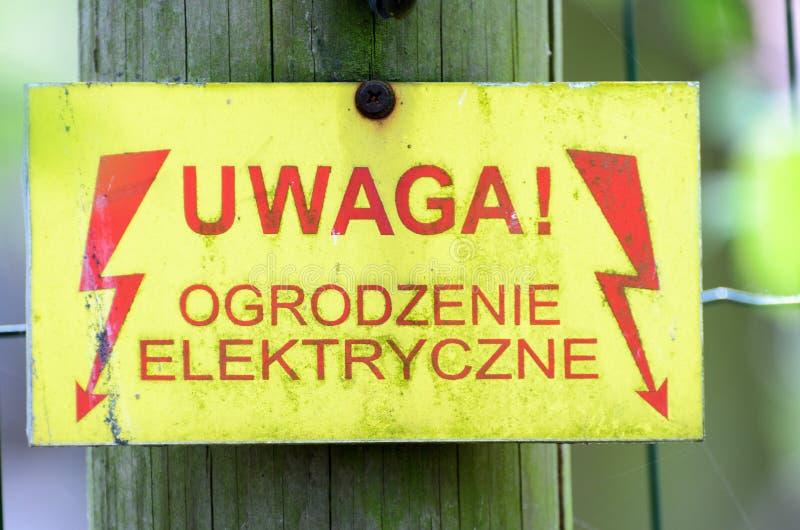 Предупредительный знак с в реальном маштабе времени обнести польское napieciem стручка elektryczne ogrodzenie uwaga языка стоковое фото
