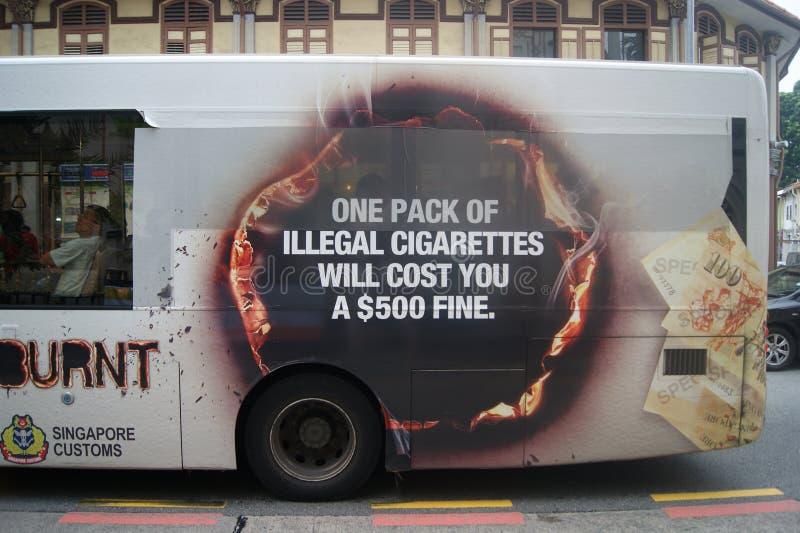 Предупреждающ на шине Сингапура, противозаконные сигареты стоковое фото