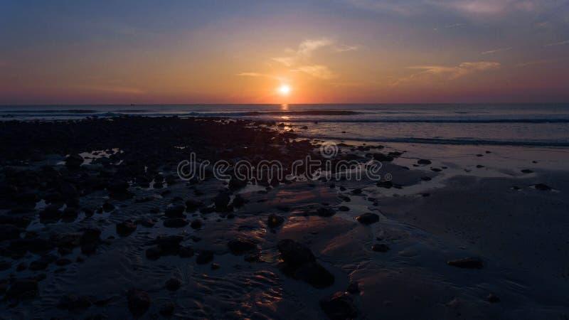 Предыдущий восход солнца на черном каменном пляже стоковые фото