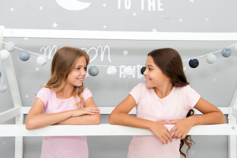 Преимущества имея сестру Сестры девушек тратят приятное время для того чтобы связывать в спальне Внушительные добавления иметь се стоковое фото rf