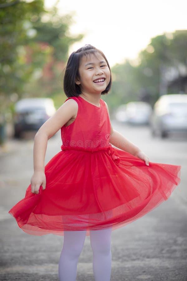 Прекрасная азиатская девушка нося красное платье юбки двигая со стороной счастья на открытом воздухе стоковые изображения rf