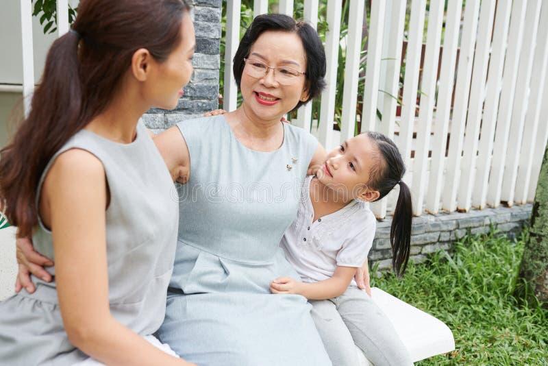Прекрасная азиатская семья сидя outdoors стоковое фото rf