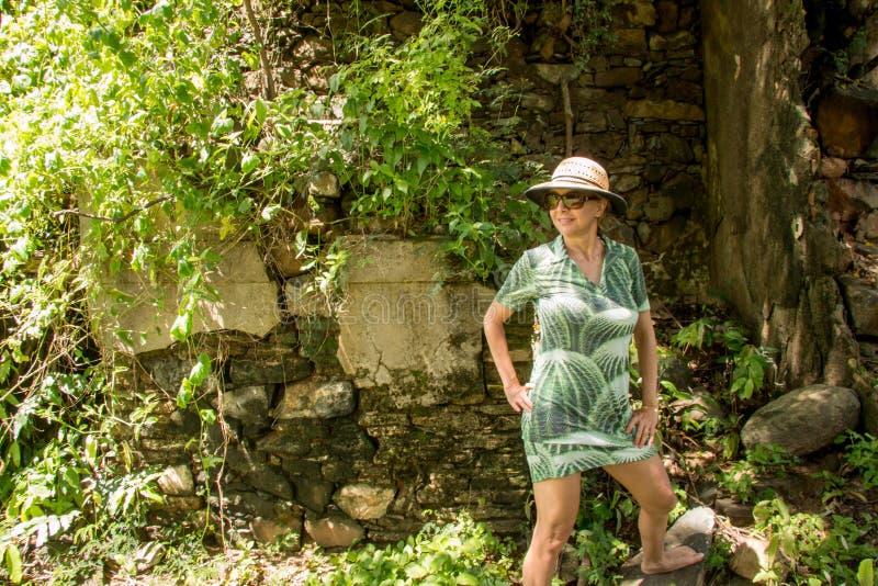 Прекрасная дама в зеленом положении на утесе стоковое фото rf