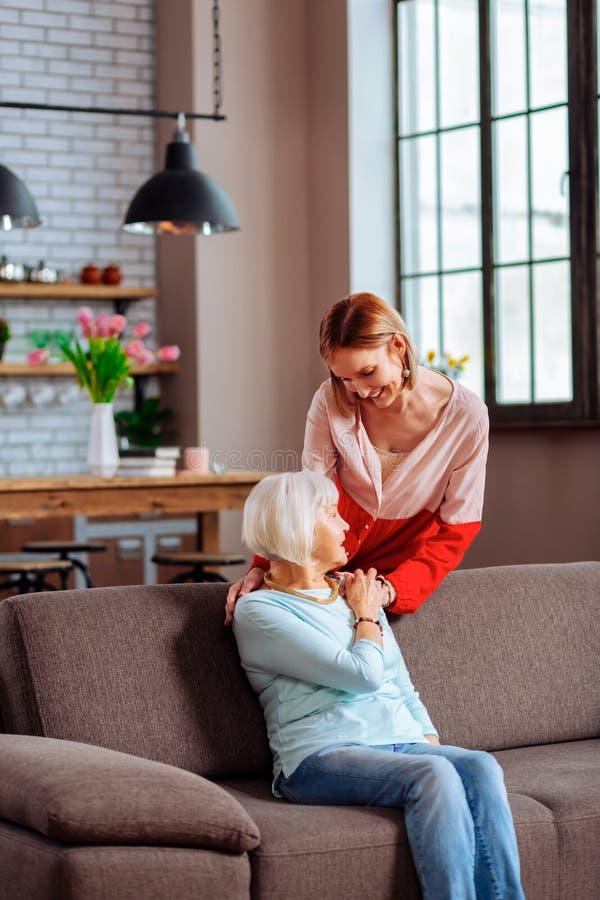 Прекрасная дама молод-взрослого мягко кладя руку на плечо матери стоковое изображение