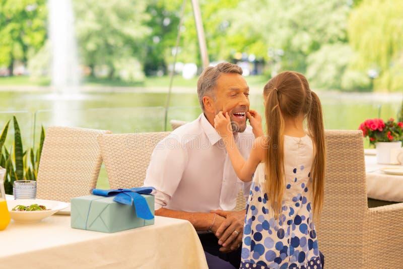 Прекрасная девушка касаясь стороне деда пока сидящ снаружи в ресторане стоковая фотография