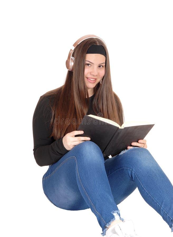 Прекрасная девушка подростка сидя на поле с наушниками и чтением стоковое изображение rf