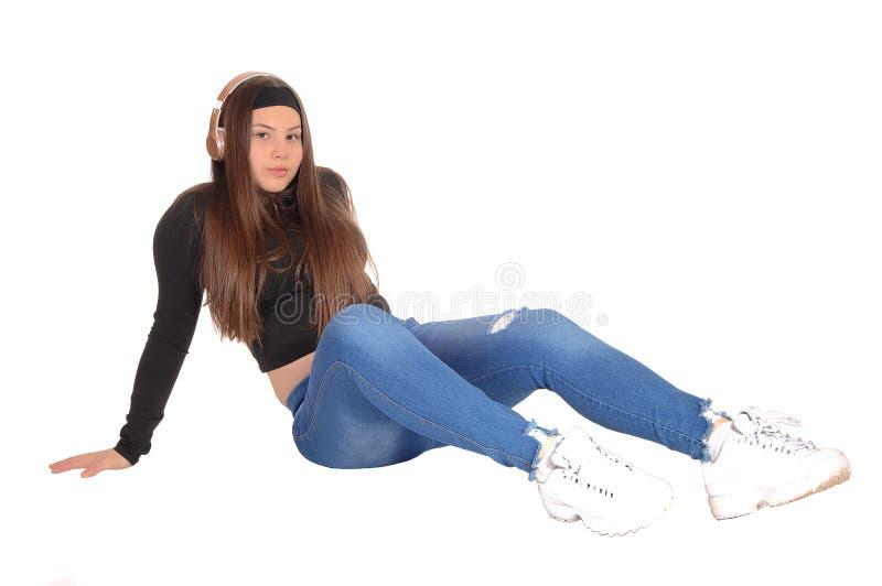 Прекрасная девушка подростка сидя на поле с наушниками стоковые изображения