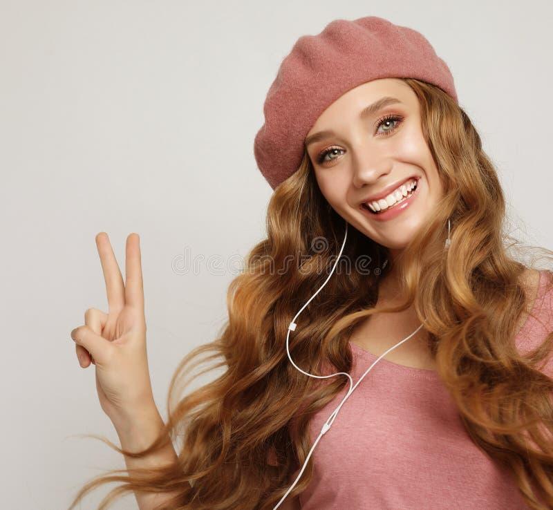 Прекрасная девушка с длинными волнистыми волосами, слушающая музыку стоковое изображение