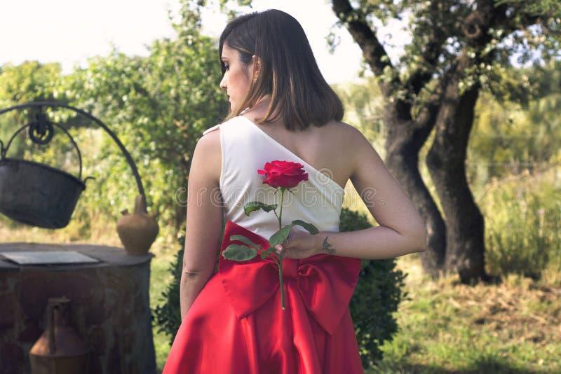 Прекрасная женщина держа красную розу на ей назад стоковое фото rf