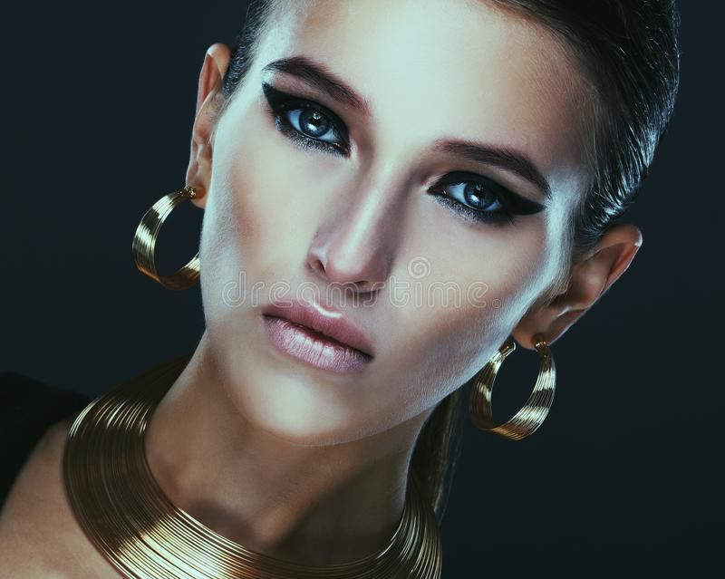 Прекрасная женщина с вечерним макияжем и золотыми украшениями стоковая фотография rf