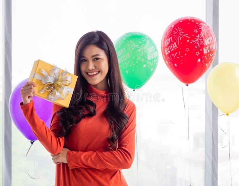 Прекрасная женщина с длинными азиатскими волосами, в свитерах с длинными рукавами, счастливо улыбающаяся Она держит подарочную ко стоковые фотографии rf