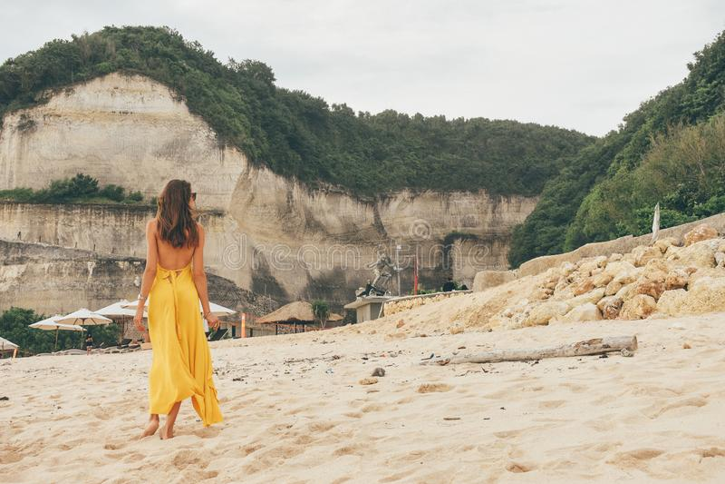 Прекрасная женщина с темными волосами в элегантной желтой одежде, ходящая по песку на Балинском пляже стоковое изображение rf