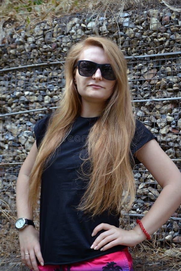 Прекрасная женщина, у нее черная футболка, солнцезащитные очки Природа Синее Солнечное небо Очень смешная концепция стоковое изображение