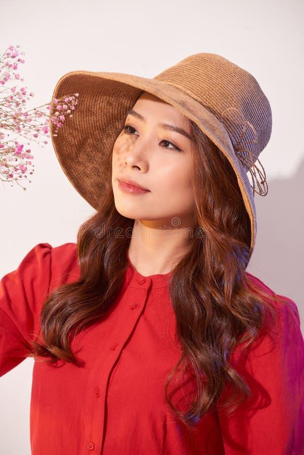 Прекрасная молодая женщина в платье и соломенной шляпе лета представляя пока держащ цветки букета стоковое фото rf