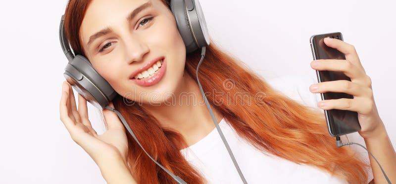 Прекрасная молодая женщина наушников слушает музыку на белом фоне стоковая фотография rf