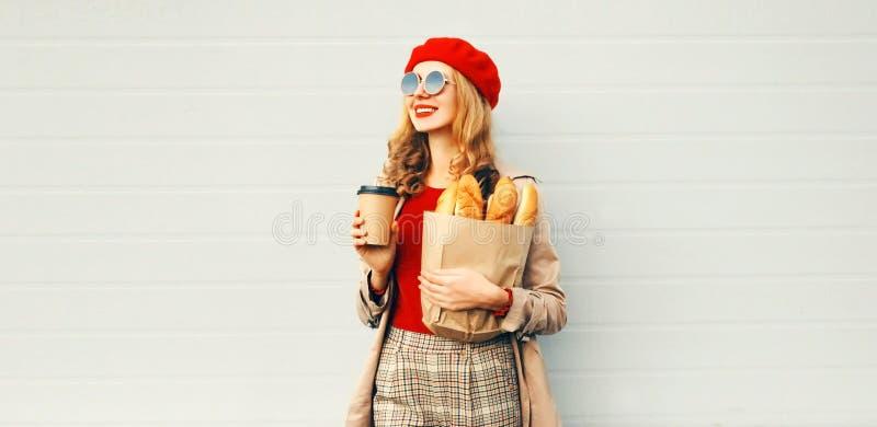 Прекрасная молодая улыбающаяся женщина, держащая кофе-чашку, продуктовую сумку с длинной белой багеткой, смотря вдаль стоковые фотографии rf