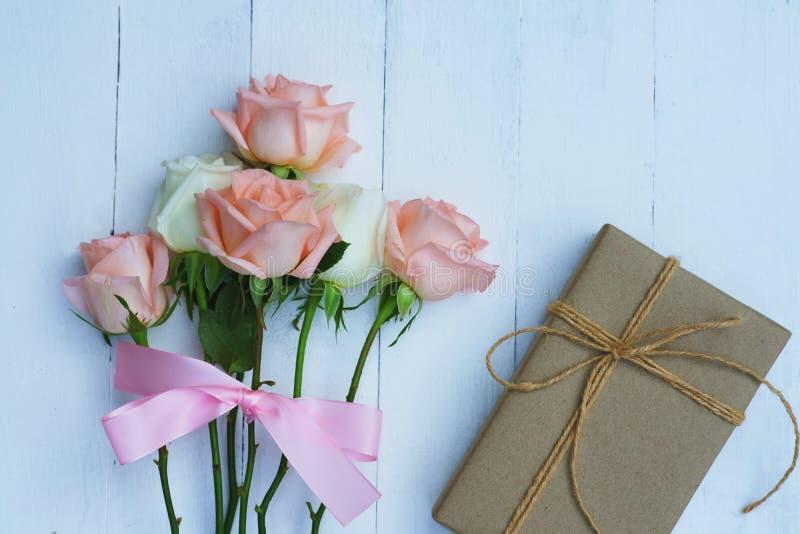 Прекрасная мягкая оранжевая розовая роза цвета связанная розовой лентой и коричневой подарочной коробкой на белой деревянной пред стоковое изображение