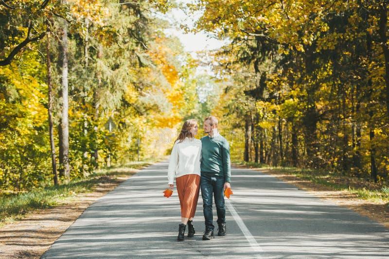 Прекрасная пара, идущая по асфальт-роуду в осеннем цветном парке стоковая фотография