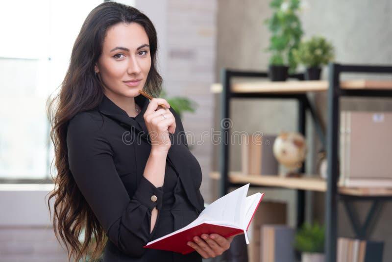 Прекрасная стильная деловая женщина в офисе делает важные записи в кра стоковое фото