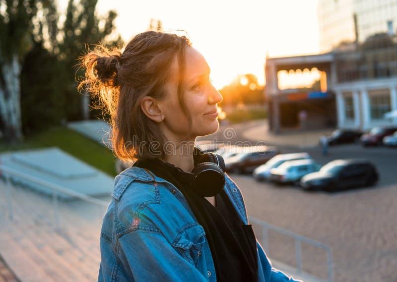 Прекрасное молодое положение девушки хипстера во время захода солнца лета стоковые фотографии rf