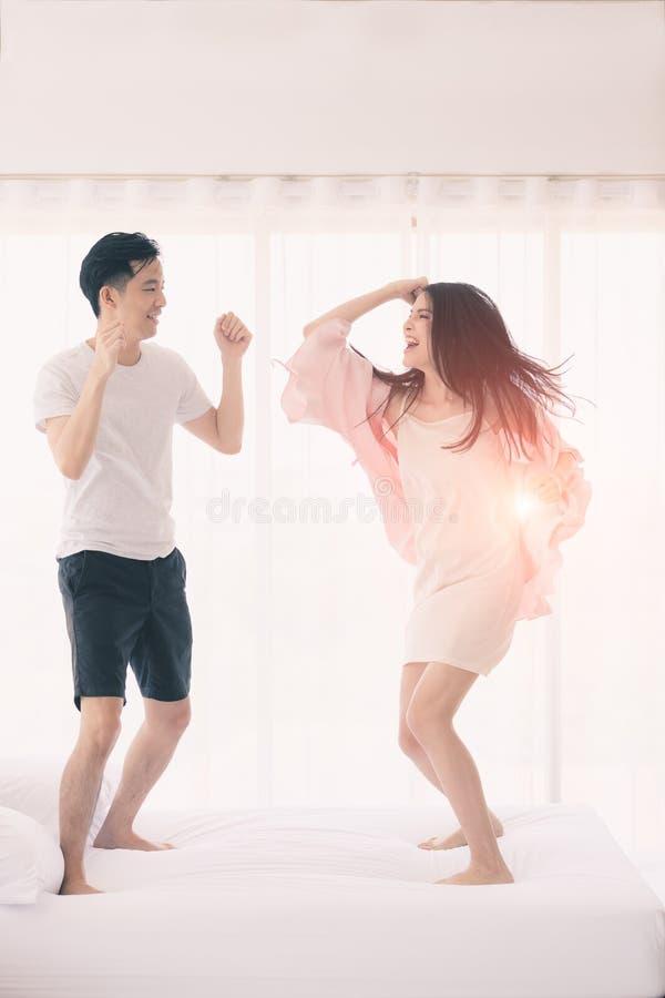 Прекрасные азиатские пары скача на кровать в спальне стоковое изображение