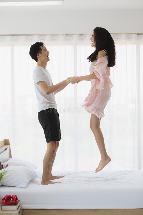 Прекрасные азиатские пары скача на кровать в спальне стоковое фото rf